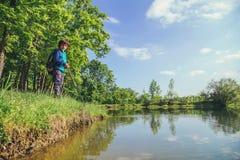在湖附近的儿童游戏钓鱼 免版税图库摄影