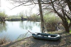 在湖附近的大橡皮艇 免版税库存照片