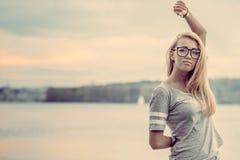 在湖附近的女孩晚上日落的 免版税图库摄影