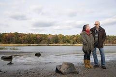 在湖附近的成熟夫妇 免版税库存图片