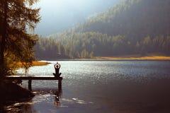 在湖附近的瑜伽 免版税库存图片