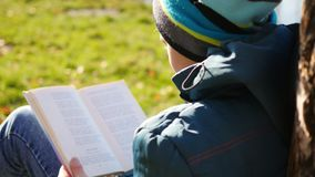 在湖附近的秋天公园读书的男孩 秋天美好的横向 学校教育 免版税库存图片