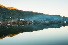 在湖附近的美丽的山村有反射的 免版税库存图片