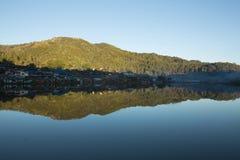 在湖附近的美丽的山村 免版税库存图片