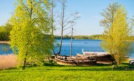 在湖附近的老小船 免版税库存图片