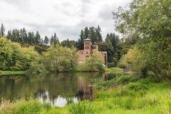 在湖附近的老砖瓦房在绿地 图库摄影