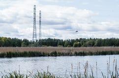 在湖附近的输电线 免版税图库摄影