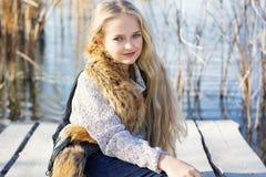 在湖附近的逗人喜爱的小女孩 库存照片