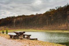 在湖附近的野餐桌在秋天森林里 库存照片