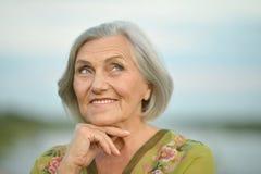 在湖附近的年长妇女 免版税库存照片