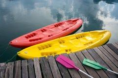 在湖靠码头的五颜六色的独木舟 库存照片
