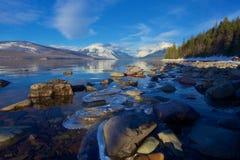 在湖麦克唐纳,蒙大拿,美国温暖的冷漠的岸的冰锁着的岩石冰川国家公园的 免版税图库摄影