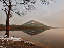 在湖,在相反银行的小山的冬天日落,冷的橙色太阳发出光线在桦树分支之间。在地面上的熔化第一雪。 库存照片