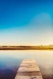 在湖,河水的老木板码头  秋天秋天森林路径季节 免版税库存图片