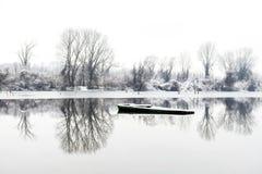 在湖结冰的被放弃的小船 库存图片