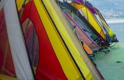 在湖水力发电岸的风帆冲浪的五颜六色的风帆在意大利 库存图片