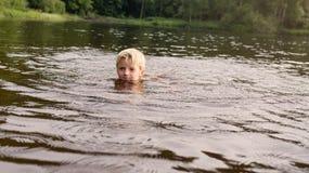 在湖黄昏的男孩游泳 库存图片