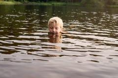在湖黄昏的男孩游泳 免版税库存图片