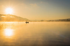 在湖Kawaguchiko,人们钓鱼在小船的, silhoue的日出 免版税库存图片
