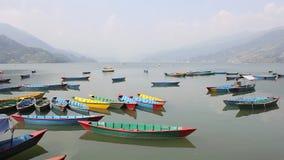在湖Phewa的空的多彩多姿的木小船一有薄雾的山谷的背景的 股票视频