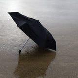在湿停车场的残破的伞。 免版税图库摄影