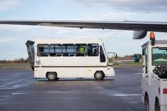 在湿机场跑道停放的乘客公共汽车 免版税库存照片