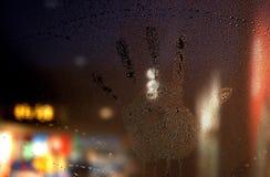在湿气被盖的窗口的手印刷品 免版税图库摄影