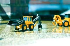 在湿水泥排队的两个民间玩具在明亮的颜色被描述 免版税库存照片