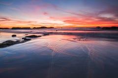 在湿沙子上的红色和蓝天日落 免版税库存图片