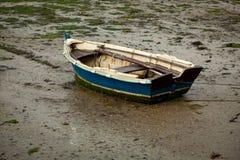 在湿沙子搁浅的一点渔船 库存照片