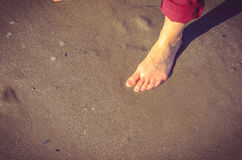在湿沙子的妇女脚 库存照片