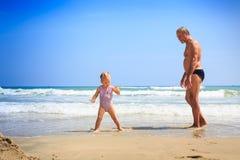 在湿沙子的小的白肤金发的女孩祖父立场由波浪海浪 图库摄影