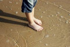 在湿沙子的男孩的脚 免版税库存照片