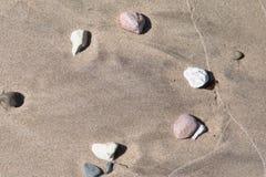 在湿沙子的石头 免版税库存照片