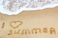 在湿沙子的题字我爱夏天 暑假概念照片 库存图片