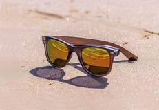 在湿沙子,海滩的太阳镜 免版税库存图片