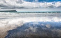 在湿沙滩反映的多云天空 免版税库存照片