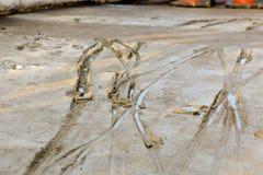 在湿混凝土的轮胎轨道 免版税库存图片