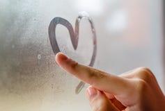 在湿窗口的小女孩drowing的心脏 免版税库存照片
