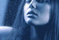 在湿玻璃后的女孩 库存照片