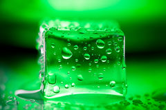 在湿玻璃桌上的色的冰块 选择聚焦 库存照片