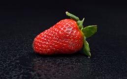 在湿黑背景的草莓 库存照片