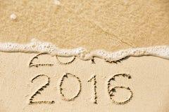 2015在湿黄色海滩沙子写的2016年题字是 库存照片