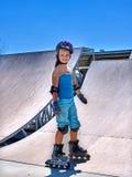在溜冰鞋的女孩骑马在skatepark 库存照片