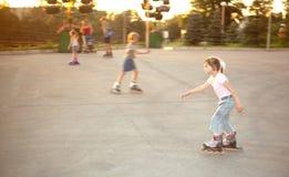 在溜冰鞋的孩子乘驾在冰鞋 免版税库存图片