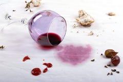 在溢出的酒杯和食物桌布的污点  免版税图库摄影