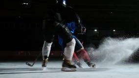 在滑冰场的双人使用的曲棍球 曲棍球战斗为顽童的两个曲棍球运动员 steadicam射击 股票录像