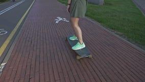 在滑板的后面看法少妇骑马 踩滑板的慢动作户外 股票视频