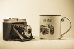 在滑稽的咖啡杯旁边的古色古香的照相机 图库摄影