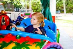 在滑稽的汽车的可爱的小的小孩女孩骑马在环形交通枢纽转盘在游乐场 愉快的健康小孩子 免版税库存照片